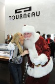 Kristin Chenoweth and Santa Claus share a kiss under the mistletoe.