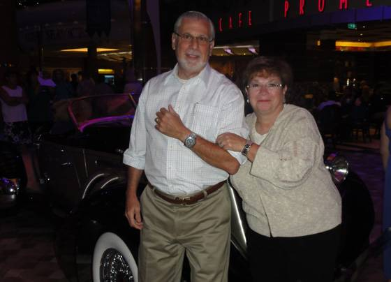Bruce Fonoroff and wife Margo Fonoroff pose in front of a 1936 Auburn Speedster Tribute  while on a cruise. Bruce is wearing a Breitling Transocean Chronograph and Margo, a Patek Phillipe Model Twenty-four.